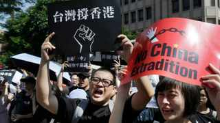 """Hong Kong students and Taiwan supporters hold up cards which read """"Taiwan Support Hong Kong"""" and """"No China Extradition"""" to support Hong Kong protesters against an extradition law outside of the Legislative Yuan in Taipei, Taiwan. Student unions from two Hong Kong universities said Friday that they have turned down invitations from city leader Carrie Lam for talks about the recent unrest. File photo: AP Photo/Chiang Ying-ying."""