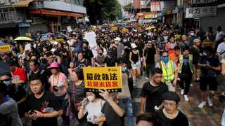 """Protesters hold up words that read: """"Strict enforcing of law against smugglers of grey goods"""" in Hong Kong. Picture: Kin Cheung/AP/African News Agency (ANA)"""