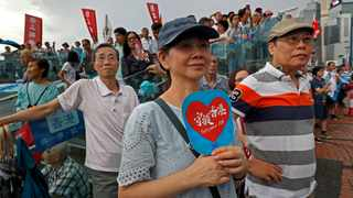 "A woman holds a fan reads ""Safeguard Hong Kong"" during a counter-rally in support of the police in Hong Kong. Picture: Vincent Yu/AP/African News Agency (ANA)"