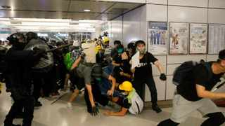 Special Tactical Squad officers attack protesters with batons who refused to disperse from a train station in Yuen Long district in Hong Kong. Picture: Eric Tsang /HK01 via AP