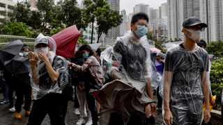 Protesters brace themselves against the strong wind and heavy rain as they gather outside the Eastern Court in Hong Kong. Picture: Vincent Yu/AP