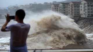 A man uses his mobile phone to record waves crashing on the shore as typhoon Lekima approaches the Shitang Township of Wenling City in eastern China's Zhejiang Province. Typhoon Lekima stuck the coast south of Shanghai, knocking down houses and trees. Picture: Han Chuanhao/Xinhua via AP