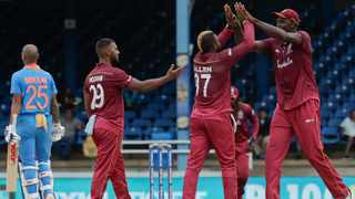West Indies bowler Fabian Allen, second right, celebrates with captain Jason Holder, right, and Nicholas Pooran, second left, after taking the wicket of India Shikhar Dhawan, right, for a 36 runs, during their third One-Day International cricket match in Port of Spain, Trinidad. Photo: AP Photo/Arnulfo Franco
