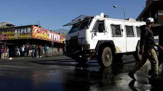 A police truck patrols an area affected by looters from a store in Germiston, east of Johannesburg. Picture: AP Photo/Themba Hadebe