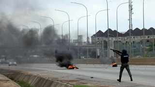 A policeman fire teargas at protesters during a protest in Abuja Nigeria. Picture: AP Photo