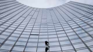 """French urban climber Alain Robert, well known as """"Spiderman"""", climbs up the 'Skyper' highrise in Frankfurt, Germany. Picture: Michael Probst/AP"""