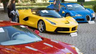People looking at a Aston Martin One-77 Coupe (2011) in front of a Ferrari LaFerrari (2015), yellow, and a Bugatti Veyron EB 16.4 Coupe (2010), blue, part of some 25 luxury cars owned by Teodoro Obiang which went on auction on Sunday. Picture: Laurent Gillieron/Keystone via AP
