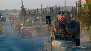 US military vehicles travel down a main road in northeast Syria. Picture: ANHA via AP