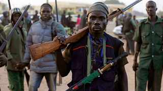 """Hunters gather during a meeting in Yolo, Nigeria. Thousands of Nigerian hunters are preparing an offensive against Boko Haram extremists, calling it """"high time"""" they help soldiers end the deadly insurgency. picture: Sunday Alamba/AP"""