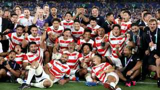 Japan players and management celebrate after defeating Scotland 28-21 in their Rugby World Cup Pool A game at International Stadium in Yokohama, Japan on Sunday. Photo: Christophe Ena/AP