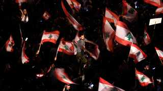 Anti-government protesters wave Lebanese flags and shout slogans against the Lebanese government during a protest in Beirut, Lebanon. Picture: AP Photo/Hassan Ammar