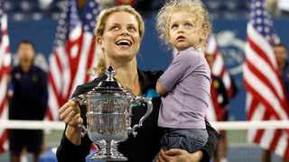 Kim Clijsters holds her daughter as she poses with her US Open trophy. Photo: Kevin Lamarque/Reuters