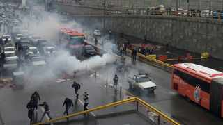 Riot police tries to disperse people as they protest on a highway against increased gas price in Tehran. Picture: Wana News Agency / Reuters.