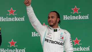 Mercedes driver Lewis Hamilton celebrates his third place on the podium of the Brazilian Formula One Grand Prix. Photo: AP Photo/Silvia Izquierdo