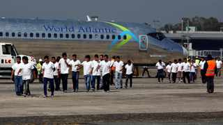 Guatemalan migrants walk on the tarmac after being deported from the US at La Aurora International airport in Guatemala City. A Honduran asylum seeker has been returned by the US to pursue asylum in Guatemala for the first time under an agreement signed in July. File photo: REUTERS/Luis Echeverria.