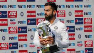 India's captain Virat Kohli walks with the trophy after their win over Bangladesh in the second test cricket match on Sunday. Photo: Bikas Das/AP