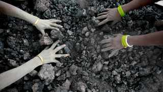 FILE - In this Monday, Dec. 14, 2015, file photo, Indian women use bare hands to pick reusable pieces from heaps of used coal discarded by a carbon factory in Gauhati, India. Inger Andersen, head of the U.N. Environment Program, says the world needs 'quick wins to reduce emissions as much as possible in 2020.' Ahead of a global climate summit in Madrid next week, her agency published a report Tuesday showing the amount of planet-heating gases released into the atmosphere hitting a new high last year. (AP Photo/ Anupam Nath, File)