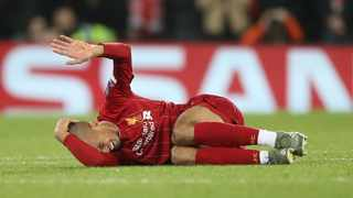 Liverpool's Fabinho lies injured before leaving the game during the Champions League Group E soccer match between Liverpool and Napoli at Anfield stadium in Liverpool, England, on Wednesday. Photo: AP Photo/Jon Super