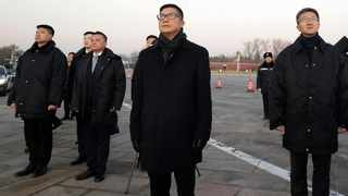 """In this photo released by Xinhua News Agency, Hong Kong new Police Chief Chris Tang, center, stands with officials as they watch a flag raising ceremony at Tiananmen Square in Beijing, Saturday, Dec. 7, 2019. Chris Tang, said Saturday in Beijing that he'll adopt both """"hard and soft approaches"""" for policing protests. He spoke to the media after his first meetings with Chinese officials since his appointment last month. (Yin Gang/Xinhua via AP)"""