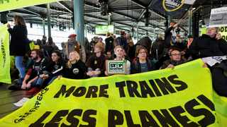 People demonstrate as Greenpeace stages a climate protest at Amsterdam Schiphol Airport in Schiphol. When it comes to climate change, Greenpeace is a leading Action Now! radical group, while the Green Party is becoming ever more moderate. Photo: Reuters