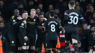 Manchester City's Kevin De Bruyne celebrates with team-mates after scoring their third goal during their Premier League game against Arsenal at the Emirates Stadium in London on Sunday. Photo: Hannah McKay/Reuters