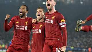 Liverpool's James Milner, second left, celebrates with his teammates Georginio Wijnaldum and Jordan Henderson after scoring his side's second goal against Leicester City at the King Power Stadium in Leicester on Thursday. Photo: Rui Vieira/AP