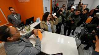 Jackie Ryan of Forest Park becomes the first person in Illinois to purchase recreational marijuana as she purchases marijuana products from employee Brea Mooney left, at Sunnyside dispensary in Chicago. Picture: Paul Beaty/AP