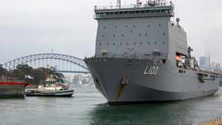 HMAS Choules departs from a fleet base in Sydney. Australia is deploying military ships to help communities ravaged by wildfires that destroyed homes and sent thousands of residents and holidaymakers fleeing to the shoreline. Picture: ABIS Benjamin Ricketts/ADF via AP