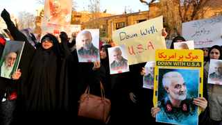 Protesters chant slogans and hold up posters of Gen. Qassem Soleimani during a demonstration in front of the British Embassy in Tehran. Picture: Ebrahim Noroozi/AP