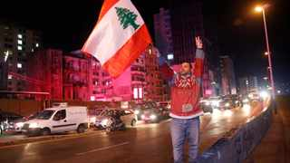 An anti-government protester flashes the victory sign and waves a Lebanese flag, as other protesters block a main road in Beirut during ongoing protests against the ruling elite. Picture: Hussein Malla/AP