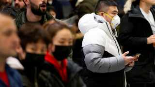 People waiting for passengers wear masks at Pearson airport arrivals shortly after Toronto Public Health received notification of Canada's first presumptive confirmed case of coronavirus. Picture: Carlos Osorio/Reuters