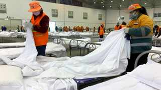 Workers arrange beds in a convention centre that has been converted into a temporary hospital in Wuhan in central China's Hubei Province. The rand is walking tall after a report on Wednesday that a treatment for the coronavirus had been found made its way to the market, restoring risk appetite and subsequently positive sentiment towards emerging markets. Photo: Chinatopix via AP