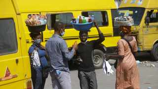 People wearing face masks sells snacks and water to passengers at Obalende bus station in Lagos Nigeria, Tuesday May 5, 2020.   (AP Photo/Sunday Alamba)