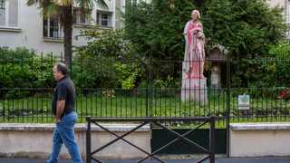 A man walks past a statue of Voltaire, a leading thinker and writer of the French Enlightenment, who owed part of his fortune to colonial-era trade, Monday, June 22, 2020. Two statues related to France's colonial era were covered in graffiti Monday amid a global movement to take down monuments to figures tied to slavery or colonialism. (AP Photo/Rafael Yaghobzadeh)