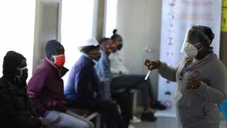 A medical worker addresses some of the first vaccine volunteers, at the Chris Hani Baragwanath hospital in Soweto, Johannesburg Wednesday, June 24, 2020. Africa's first participation in a COVID-19 vaccine trial has begun as volunteers received injections developed at the University of Oxford in Britain. The large-scale trial is being conducted in South Africa, Britain and Brazil. (AP Photo/Siphiwe Sibeko)