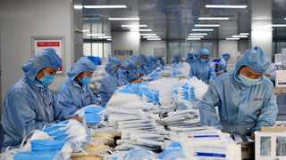 Workers make face masks at the workshop of a company in Changyuan, central China's Henan Province. Picture: Hao Yuan/Xinhua