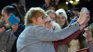 British singer-songwriter Ed Sheeran poses with a fan. Picture: Stefanie Loos/AFP