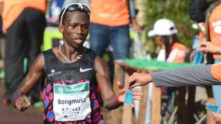 Bongmusa Mthembu snatches a final hydration sachet as he powers to victory. Photo: Stephen Granger
