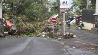 People stand by fallen trees in Moroni after Cyclone Kenneth hit Comoros. Picture: Ibrahim Youssouf/AFP