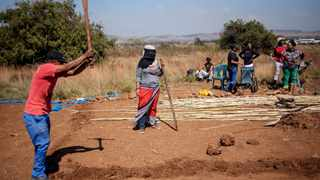 Members of the Coloured community of Eldorado Park prepare a clearing in a plot of land during a land grabbing action on the outskirts of Johannesburg. Picture: Michele Spatari / AFP