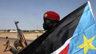 An SPLA soldier is pictured behind a South Sudan flag as he sits on the back of a pick-up truck in Bentiu, Unity state, file.    REUTERS/Andreea Campeanu