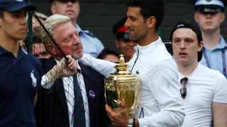 Novak Djokovic holds the winner's trophy as he is congratulated by German former player Boris Becker at Wimbledon on Sunday. Photo: EPA/Adrian Dennis