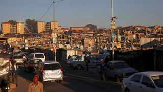 Locals walk on the streets of Alexandra Township, an informal settlement located near the upper-class suburb of Sandton in Johannesburg. Picture: Reuters/Siphiwe Sibeko