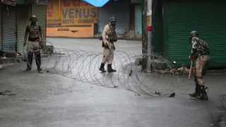 Indian paramilitary soldiers close a street using barbwire in Srinagar, Indian controlled Kashmir, Saturday, Aug. 10, 2019. Authorities enforcing a strict curfew in Indian-administered Kashmir will bring in trucks of essential supplies for an Islamic festival next week, as the divided Himalayan region remained in a lockdown following India's decision to strip it of its constitutional autonomy. The indefinite 24-hour curfew was briefly eased on Friday for weekly Muslim prayers in some parts of Srinagar, the region's main city, but thousands of residents are still forced to stay indoors with shops and most health clinics closed. All communications and the internet remain cut off. (AP Photo/Mukhtar Khan)
