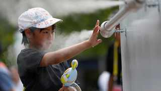 A visitor experiences a large-scale misting tower dispensing ultra-fine mist during a proving test of heat countermeasures for the Tokyo 2020 Olympic and Paralympic Games. Photo: Reuters/Issei Kato