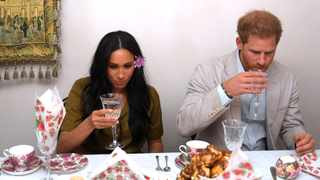 Prince Harry and his wife Meghan, take a drink as they visit a family in the Bo Kaap district of Cape Town. REUTERS/Toby Melville