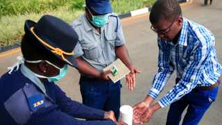 A police officer shows a visitor how to disinfect his hands against the spread of coronavirus disease (Covid-19) at State House in Harare, Zimbabwe. Picture: Philimon Bulawayo/Reuters