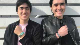 Entrepreneurs Matthew Toles and Joseph Toles, co-founders of the company Slightly Robot, show smartbands which buzz when the wearer's hand goes near their face. Picture: Immutouch/Handout via Reuters