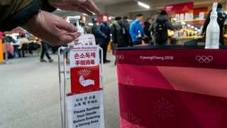 A man sanitizes his hands at the entrance to the media cafeteria at the Pyeongchang Olympics. Photo: Paul Chiasson/AP