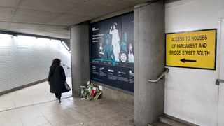 A passenger walks past a collection of votive flowers and messages where Marcos Amaral Gourgel was found dead on February 14, 2018 in the underpass at Westminster Underground Tube station near the Houses of Parliament in London. Picture: AFP/ Justin Tallis